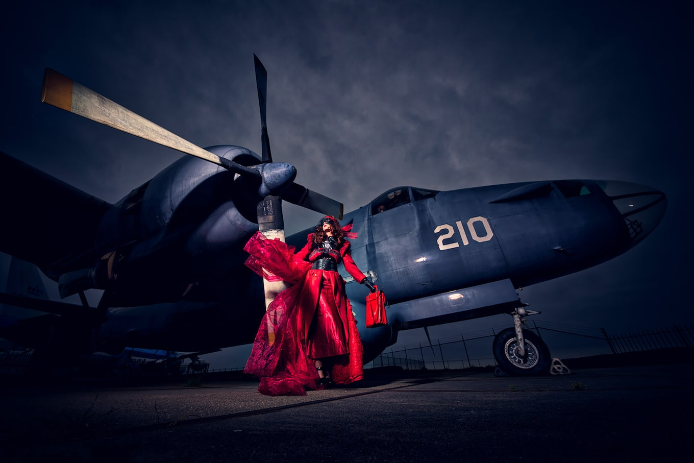Frank-Doorhof-sony-alpha-7RII-model-wearing-red-dress-standing-in-front-of-old-aeroplane
